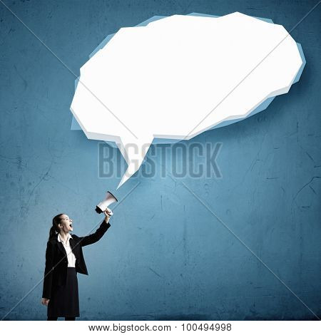 Young businesswoman with megaphone in hand and speech bubble above