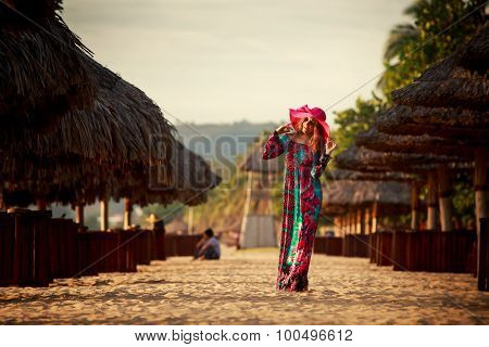 Slim Girl In Long And Big Red Hat Stands Among Beach Umbrellas
