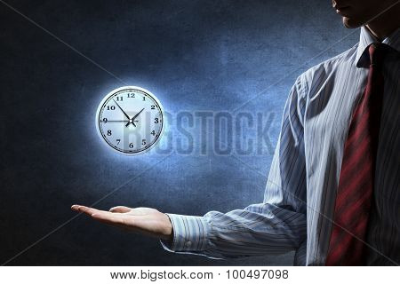 Close up of businessman holding clock sign in palm