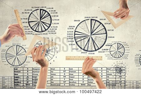 Close up of hand measuring diagrams with ruler