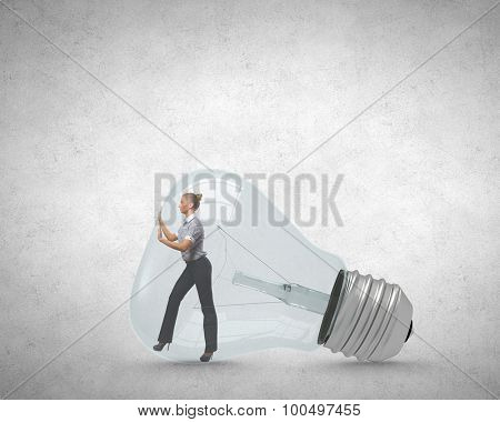 Businesswoman inside light bulb trying to get out