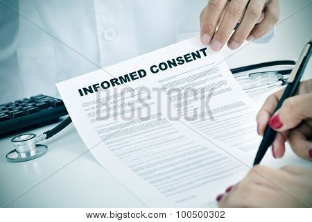closeup of a young woman patient signing an informed consent at the doctors office