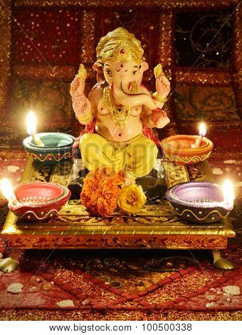 Small statue of Lord Ganesha. Pooja arrangement at home during Ganesh Festival in India.
