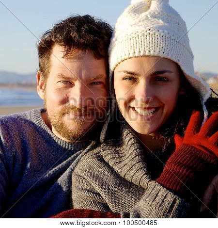 Happy Smiling Couple In Front Of Beach Looking Camera During Sunset