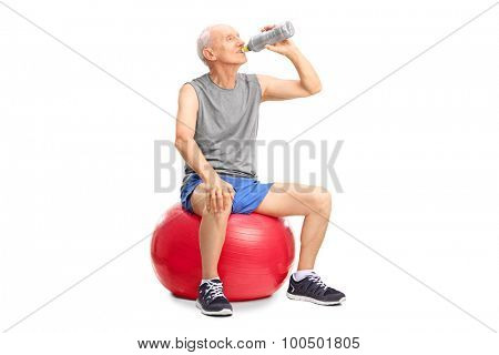 Studio shot of a senior man sitting on a red fitness ball and drinking water isolated on white background