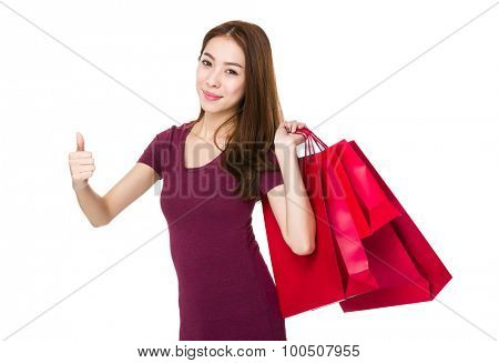 Woman with shopping bag and thumb up gesture