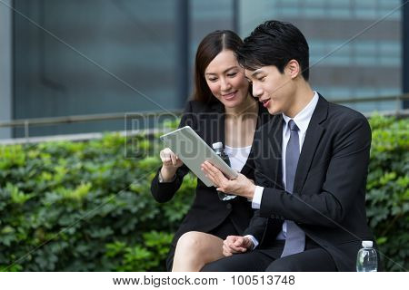 Two business people using the tablet for report