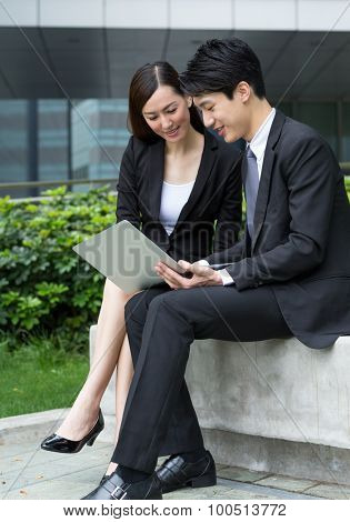 Two business people discuss about the report at outdoor