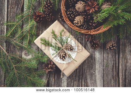 Hand crafted gift on rustic wooden background with with fir branches and cones