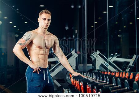 Male athlete with a dumbbell in the gym lean on row