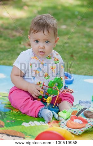 Baby, less than a year old   playing with  toy
