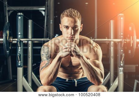 Closeup portrait of a muscular man workout with barbell at gym. He is sitting in the frame view, thi