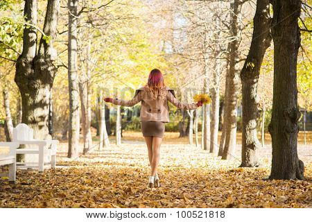 Beautiful girl walking in the park with a bouquet of leaves.