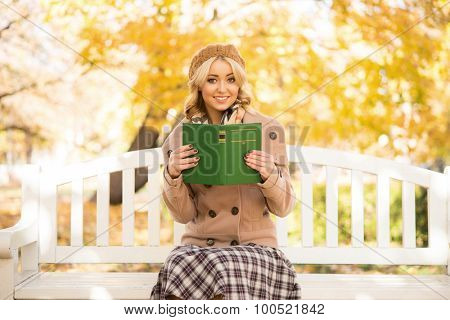Beautiful smiling young woman sitting on the bench in autumn and reading a novel book.