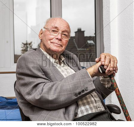 Smiling Senior Man Sits At The Chair
