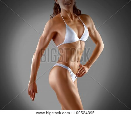 Muscular Athletic Young Woman In A White Bathing Suit On A Gray Background. Fitness. Muscular Body.
