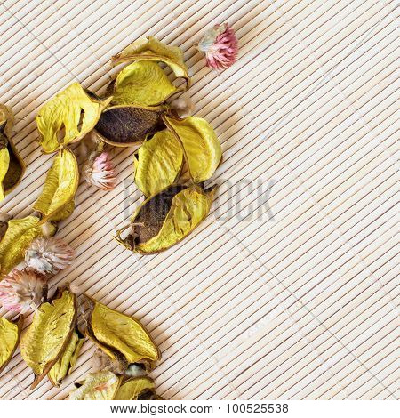Dry flower petals on bamboo mat background