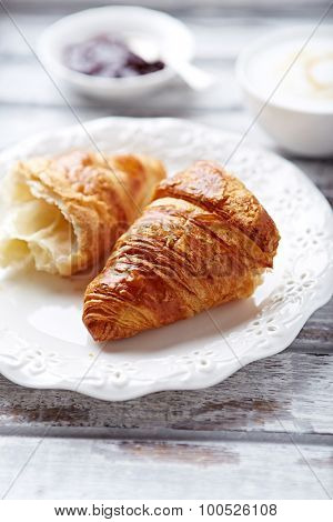 Croissant, cappuccino and cherry jam