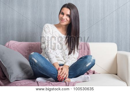 Relaxing At Home, Comfort. Cute Young Woman Smiling, Sitting Cross-legged  On White Couch, Sofa  At