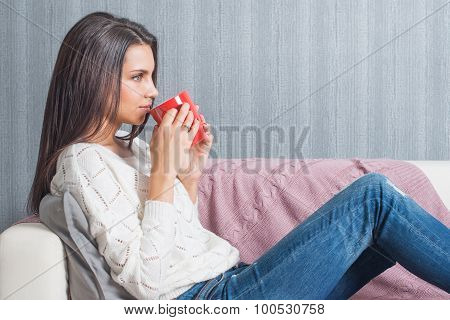 A Woman  Raising A Red Mug With Coffee, Tea To His Lips Smiles Lying On The Couch, Sofa