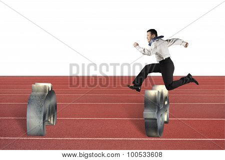 Man Jumping Over Currency Symbol Obstacles On Track
