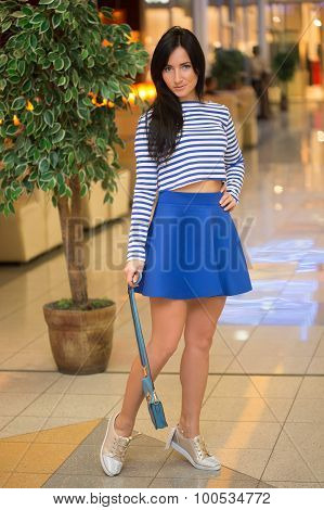 girl in a striped blouse with a bag walks around the store.
