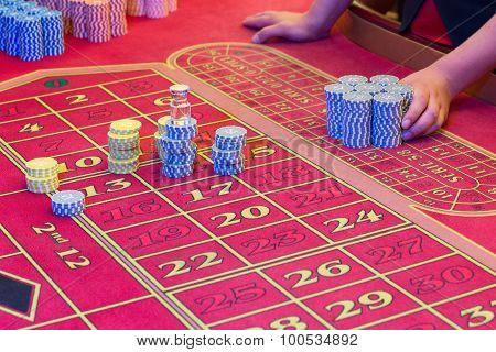 Casino American Roulette gambling table with a playing chips on the layout. Croupier is doing payout