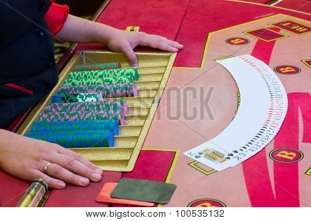 Casino dealer (croupier) spreaded the deck of cards on the Poker table