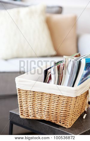 Magazines in basket on table in living room, close up
