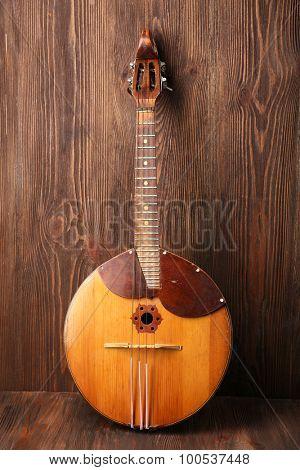 Folk musical instrument domra on wooden background