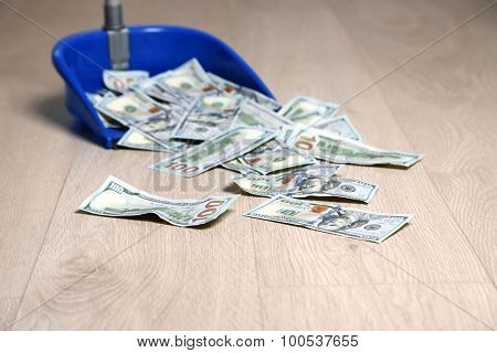 Dollars in garbage scoop on wooden floor background