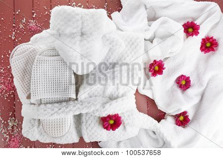 Bathrobe, towel and slippers on wooden surface, top view