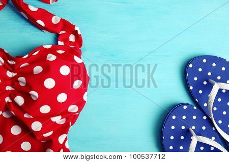 Swimsuit and flip flops on wooden background