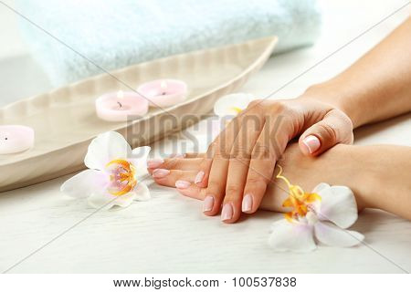 Woman hands with french manicure and orchid flowers on wooden table close-up