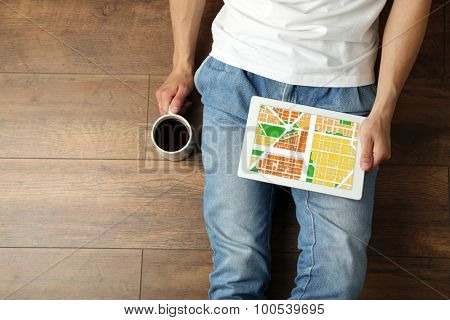 Young man sitting on floor and holding tablet with map gps navigation application