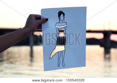 Female hand holding fashion sketch outdoors