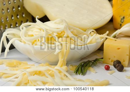 The Bowl With Grated Cheese And Spices Around