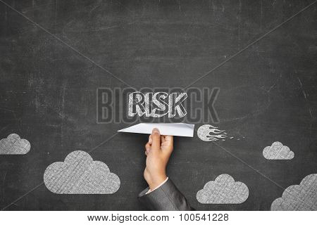 Risk concept on blackboard with paper plane