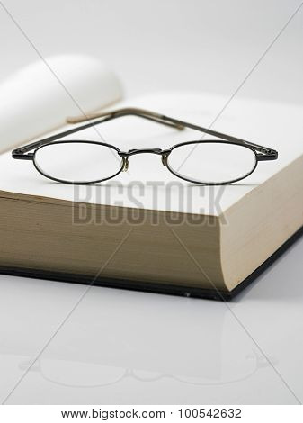 An open hardcover book with a pair of reading glasses