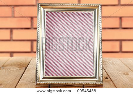 Old frame with striped canvas standing on table on brick wall background