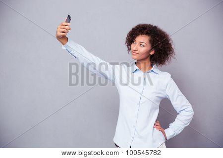 Portrait of a beautiful afro american woman making selfie photo on smartphone over gray background