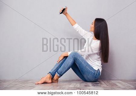 Portrait of a young woman sitting on the floor and making selfie photo on smartphone on gray background