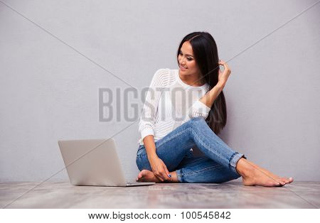 Portrait of a happy girl sitting on the floor with laptop on gray background