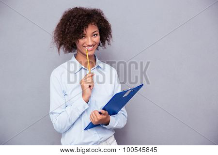 portrait of a smiling afro american woman holding clipboard with pencil over gray background