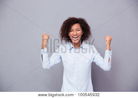 Portrait of a cheerful afro american businesswoman celebrating her success on gray background and looking at camera