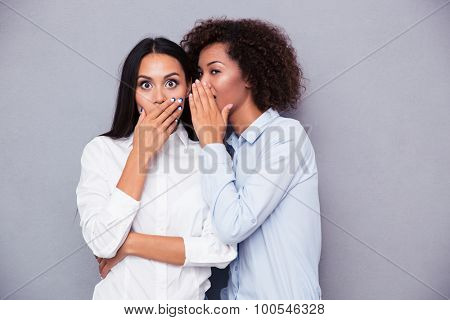 Portrait of a two girls gossip on gray background