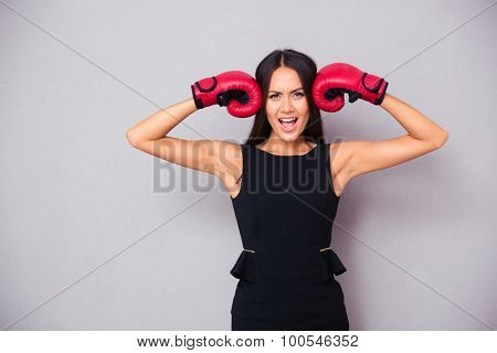Portrait of a beautiful businesswoman standing in boxing gloves on gray background