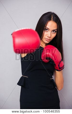 Portrait of a young businesswoman in boxing gloves punching at camera on gray background
