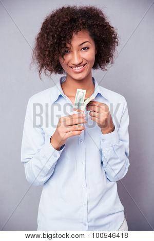 Portrait of a smiling afro american woman holding money on gray background