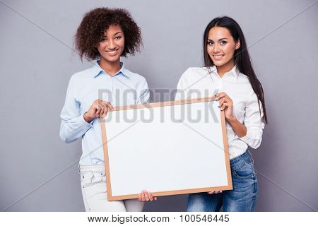Portrait of a two girls holding blank board over gray background